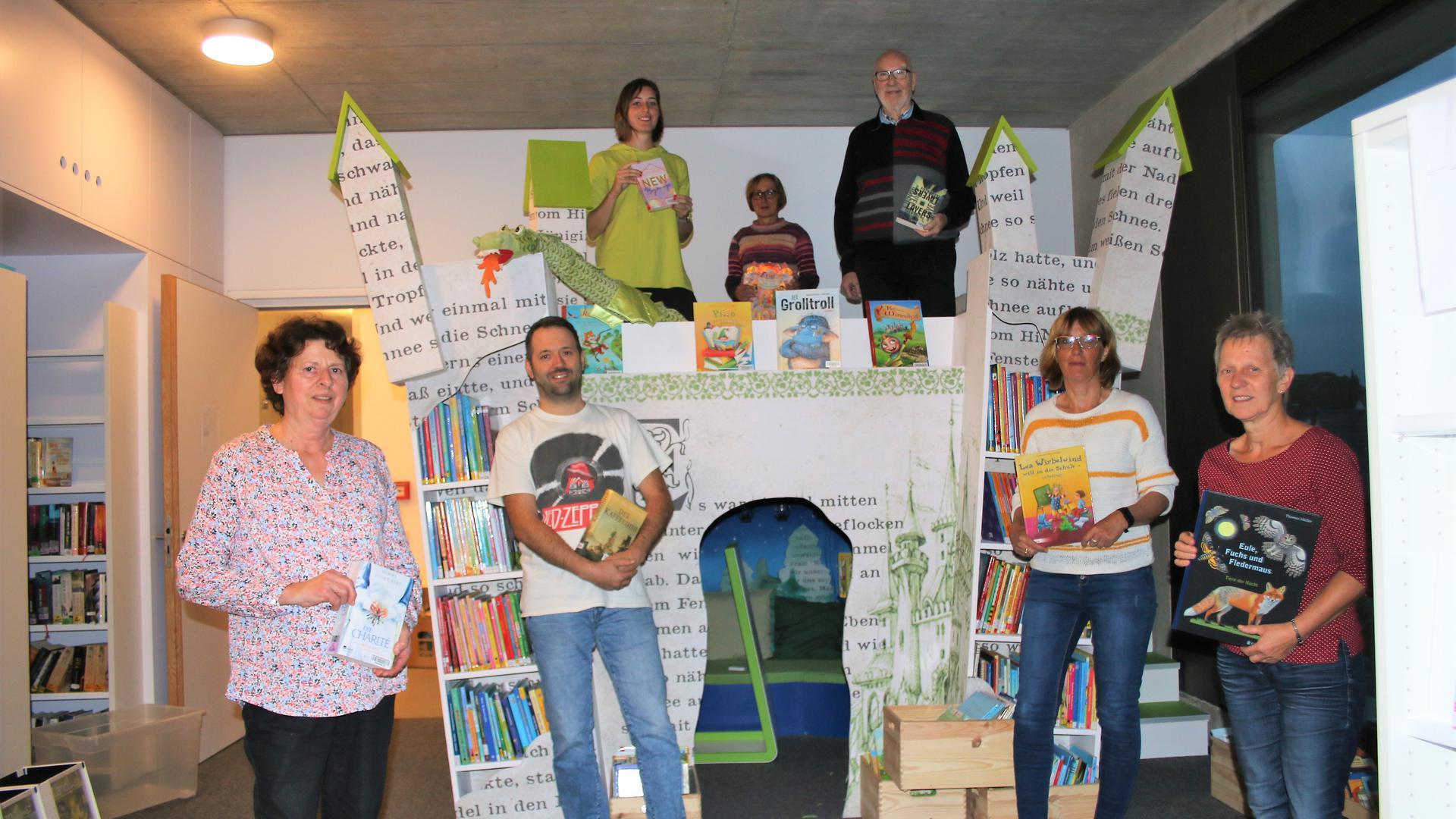 In einer  begehbaren Leseburg aus Buchseiten stehen mehrere Bücher wie in einem Regal. Von den Zinnen schauen Ehrenamtliche herunter. Auch vor der Burg stehen Ehrenamtliche.