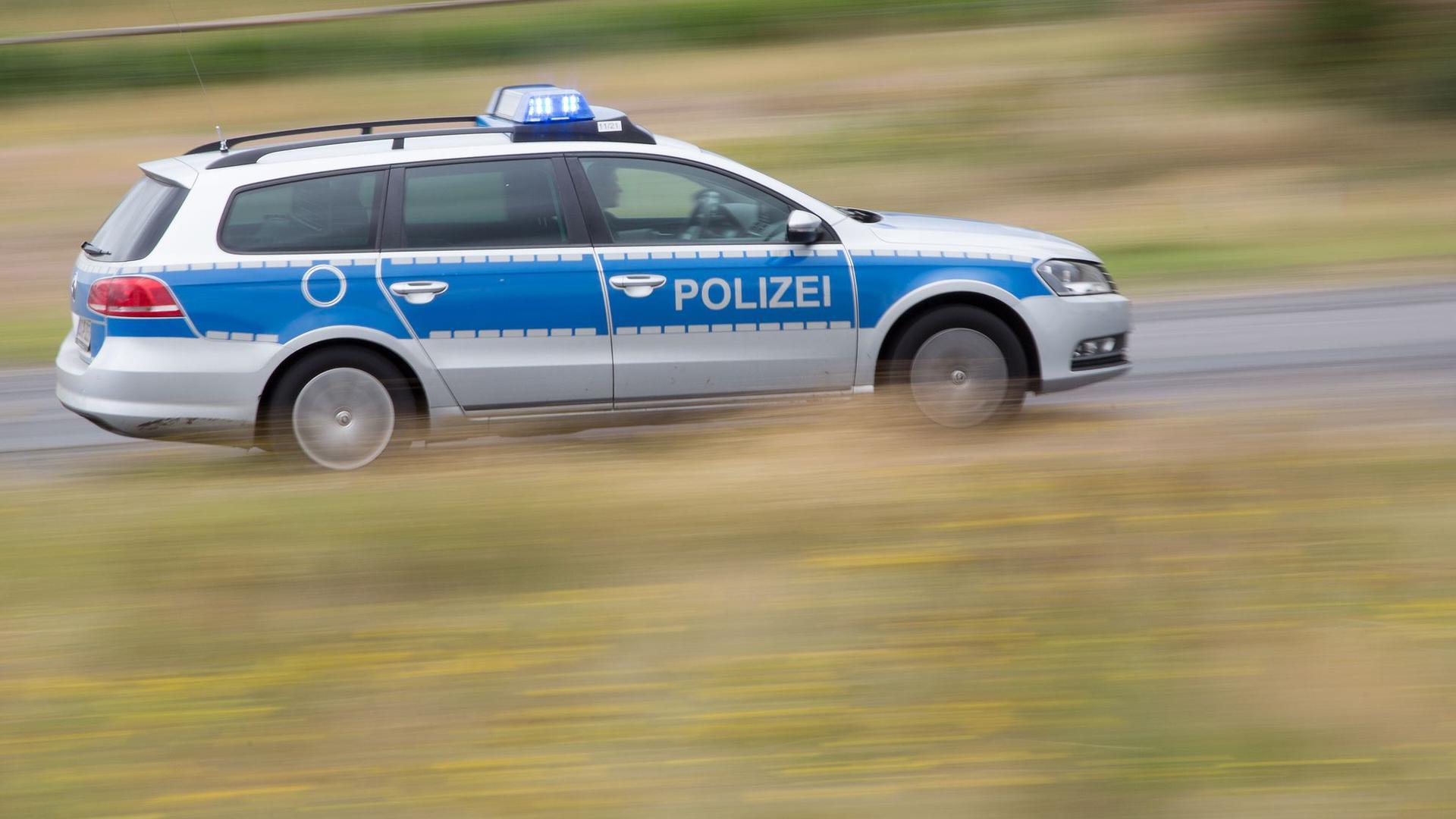 Ein Polizeifahrzeug fährt mit Blaulicht auf der Landstraße.