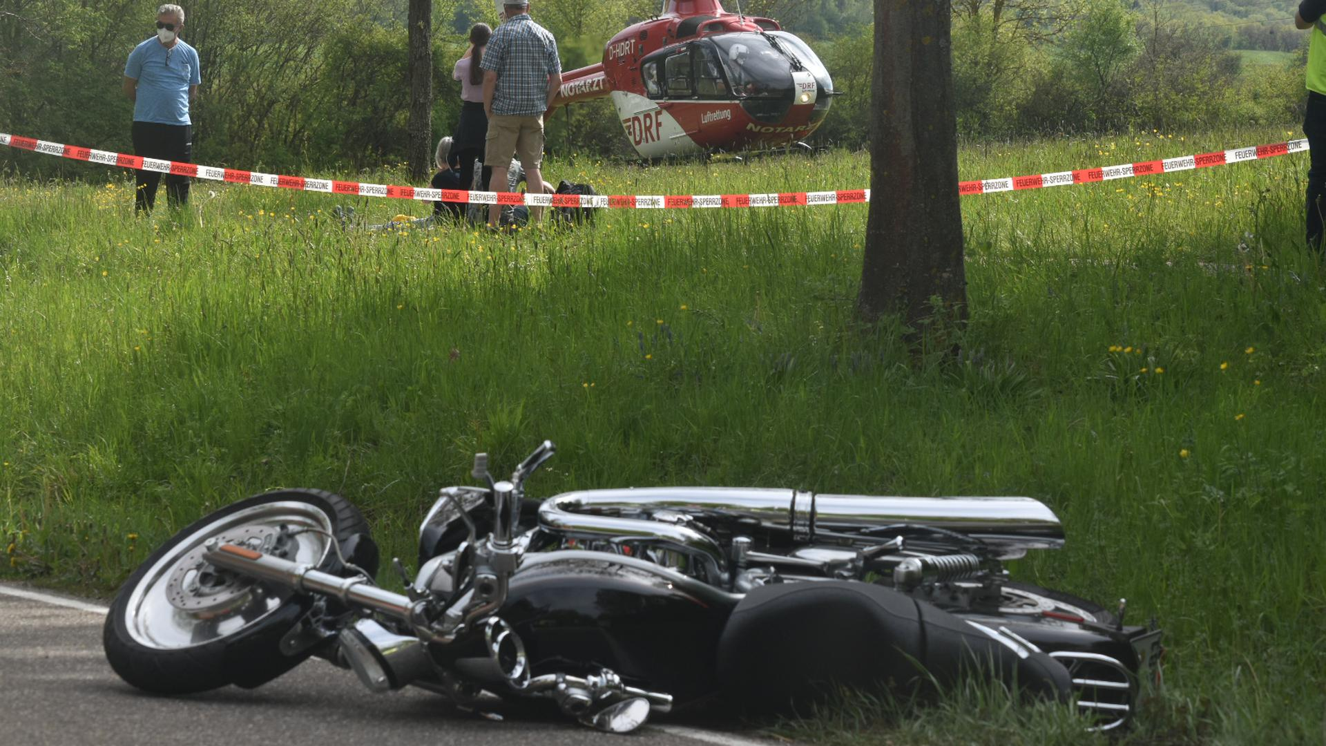Ein schwarzes Motorrad liegt auf der Straße. Im Hintergrund steht ein Rettungshubschrauber auf einer Wiese.