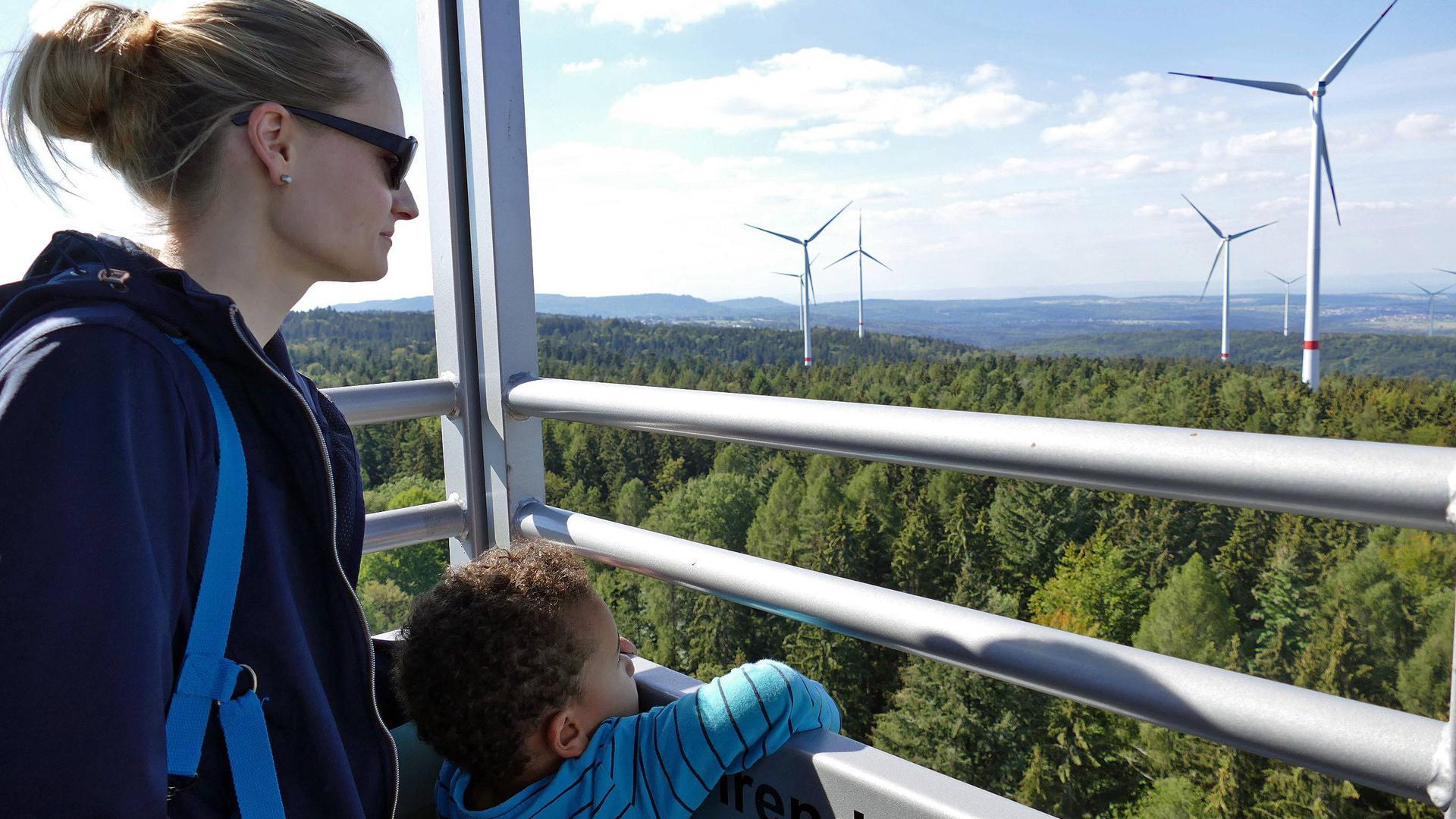 Eine Frau und ein Kind blicken auf die Anlagen im Windpark Straubenhardt.