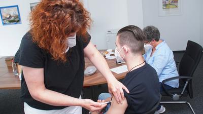 Die Spritze gegen Corona: Ute Lotz verabreicht Philipp Denninger seine Impfung, Ärztin Anna Reichert dokumentiert alles.