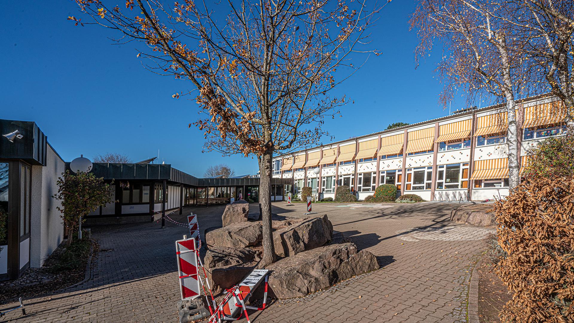 Schulgebäude von außen mit weitgehend entlaubten Bäumen