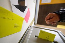 Ein Mann wirft einen Wahlbrief in eine Wahlurne