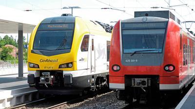 Züge von Go Ahead und Deutscher Bahn stehen an einem Bahnhof.