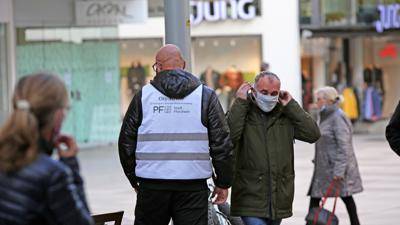 """Freundliche Ermahnung: Ein Mitarbeiter der Pforzheimer """"City-Streife"""" erinnert an die neue Maskenpflicht in der Fußgängerzone."""