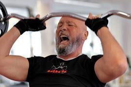 Ein Mann stemmt eine Stange mit Gewichten