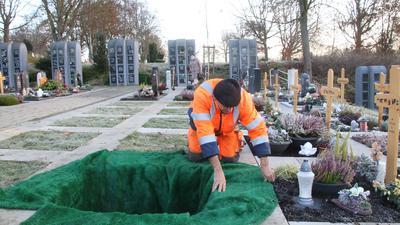 Mann in organe-weißer Berufskleidung kniet auf dem Knittlinger Friedhof und hebt ein Grab aus.