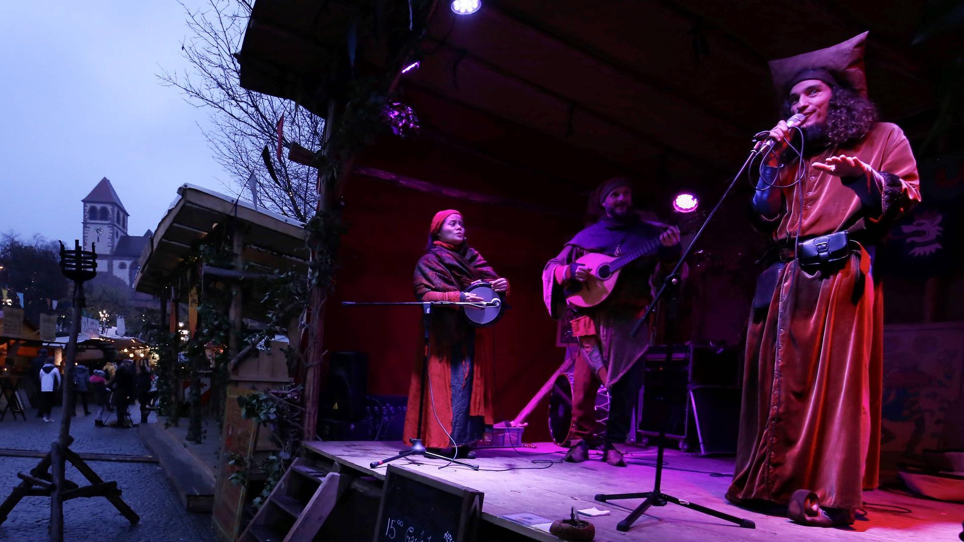 Drei Menschen zeigen auf einer Bühne auf dem Mittelaltermarkt in Pforzheim eine Musikaufführung.