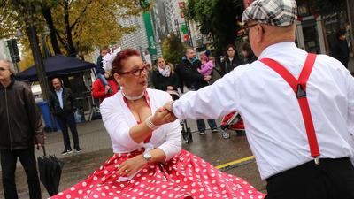Ein Mann und eine Frau im Petticoat tanzen auf einer Straße.