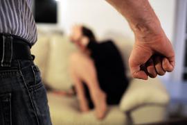 Eine Frau versucht sich vor der Gewalt eines Mannes zu schützen.