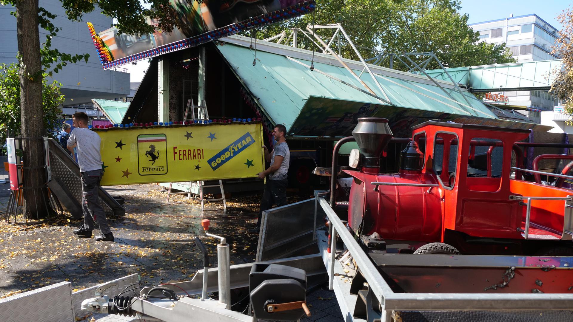 Zwei Männer tragen einen Teil des Karussels weg, im Vordergrund ist eine angekokelte Mini-Lokomotive.