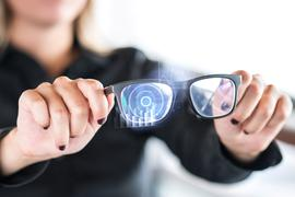 Person holding nanotech smart glasses. Eyewear with interactive augmented reality (AR) interface and screen with visual digital sensor. Futuristic cyber and nano technology. Modern nanotechnology.