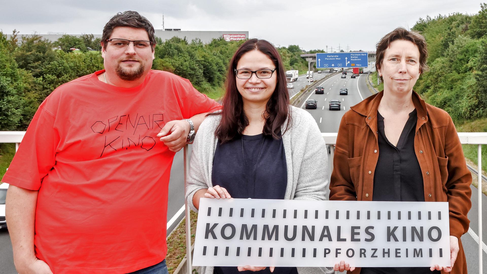 Timo Gerstel, Sarah Münzer und Christine Müh (von links) vom Kommunalen Kino Pforzheim wollen eine Vorführung an einem sehr ungewöhnlichen Ort bieten, nämlich auf der A8 bei Pforzheim, die im Hintergrund zu sehen ist.