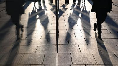 Passanten spiegeln sich bei tiefstehender Sonne in einer Schaufensterscheibe. +++ dpa-Bildfunk +++