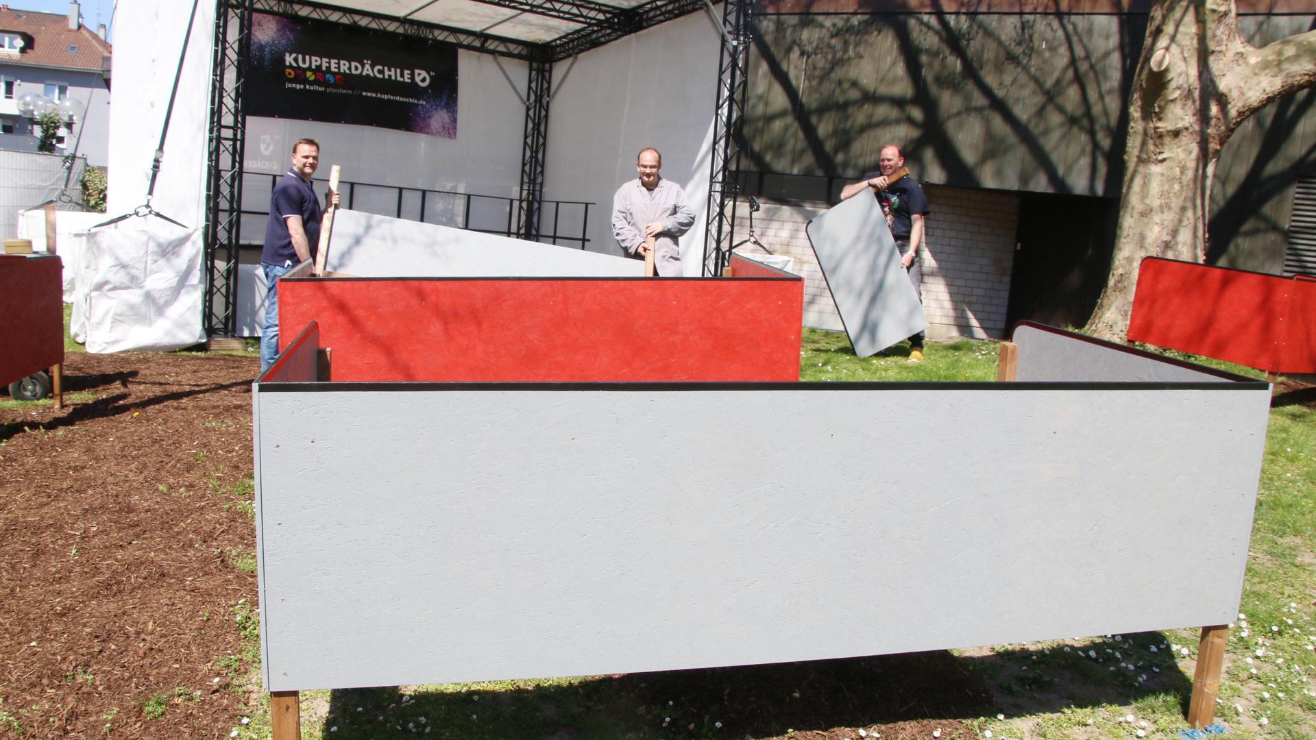 """Drei Männer stehen vor einer Open-Air-Bühne, auf der das Wort """"Kupferdächle"""" zu lesen ist und bauen davor eine große grau-rote Box auf."""