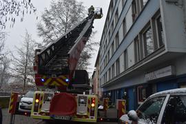 Ein Feuerwehrfahrzeug mit ausgefahrener Drehleiter bei einem Einsatz in der Pflügerstraße in Pforzheim.
