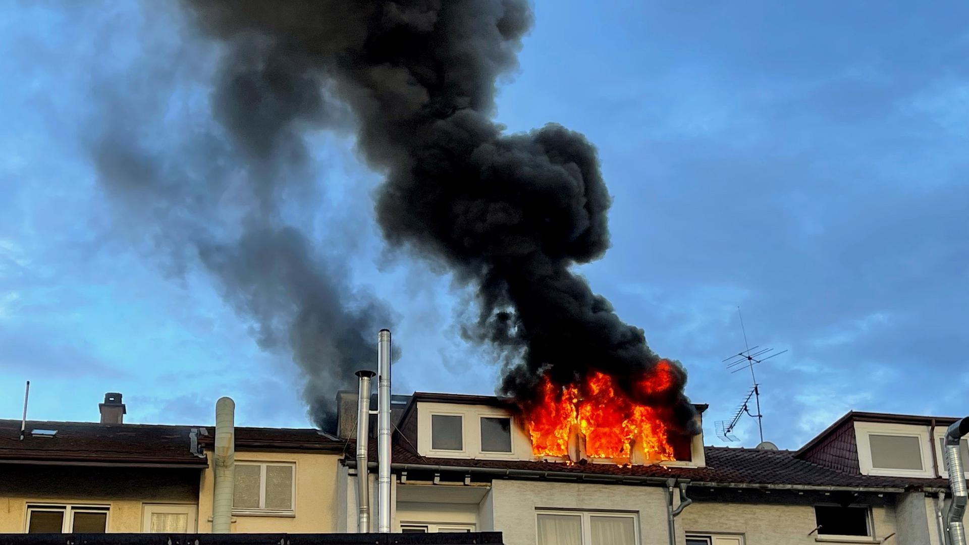 Brennender Dachstuhl eines Mehrfamilienhauses mit hoher Rauchsäule.