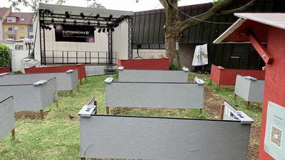 Mehrere Holzabtrennungen stehen vor einer Bühne.