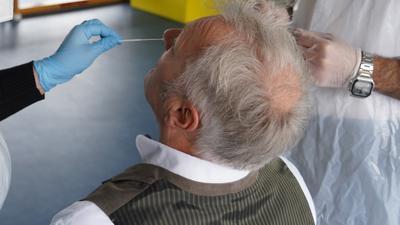 Mann bekommt im Testzentrum von Witzenmann in Pforzheim Teststäbchen in die Nase geführt
