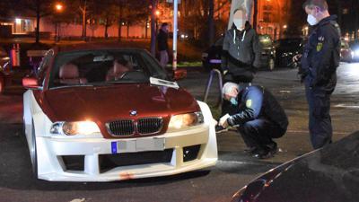 Polizisten kontrollieren ein sehr tief gelegtes Fahrzeug