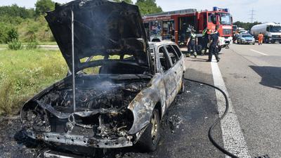 Ausgebranntes Auto und Feuerwehr im Hintergrund