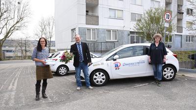 Drei Menschen vor Diakonie-Fahrzeug