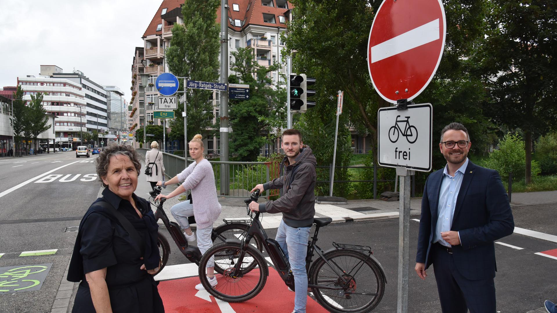 Zwei Personen auf dem Fahrrad stehen auf einem roten Radweg, zwei weitere Personen ohne Rad im Vordergrund