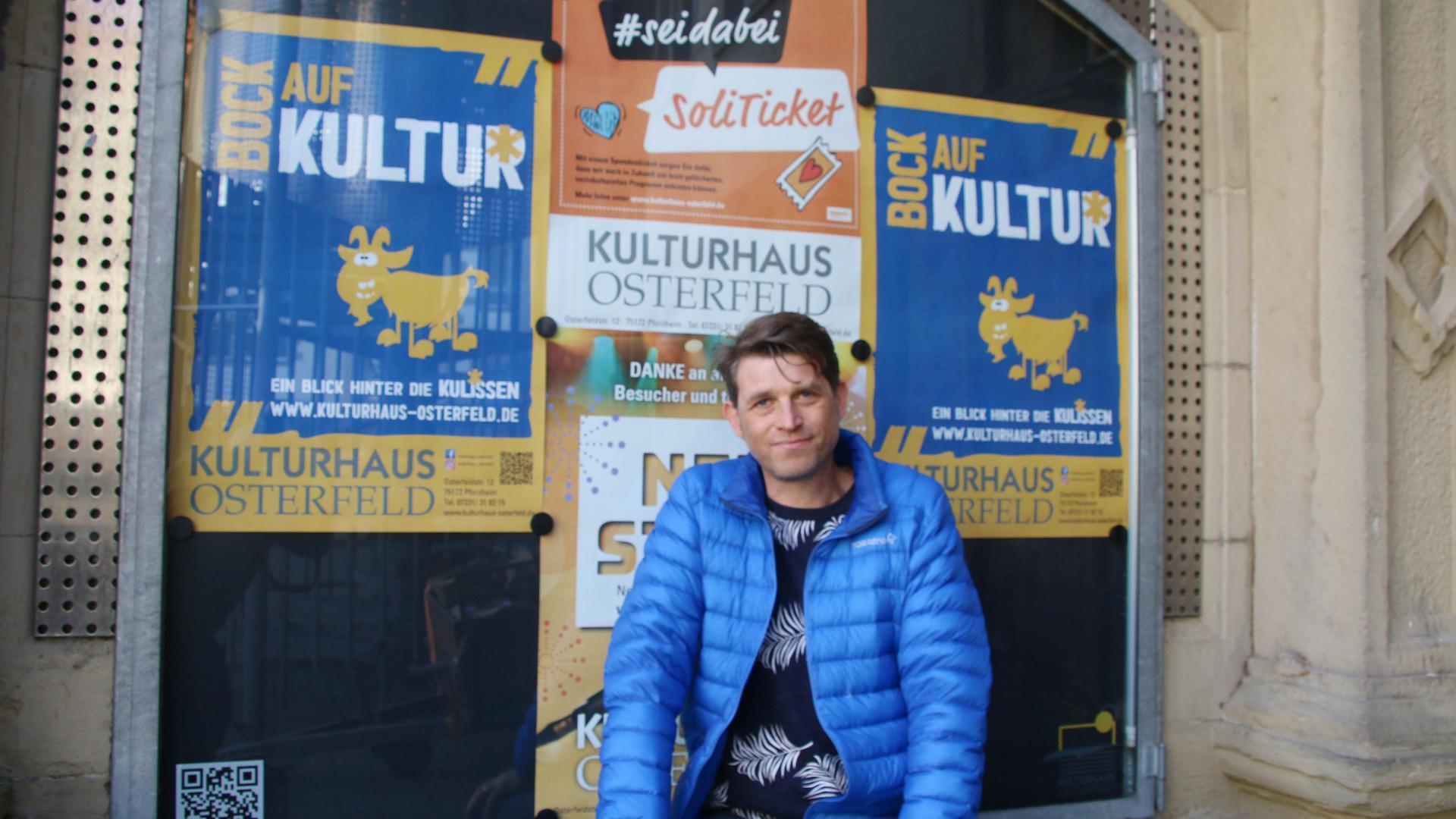 """Ein Mann in blauer Jacke sitzt vor einem schwarzen Brett, auf dem Werbeposter mit den Slogans """"Bock auf Kultur"""" zu sehen sind. Bei dem Mann handelt es sich um den neuen Leiter des Kulturhauses Osterfeld Bart Dewijze."""