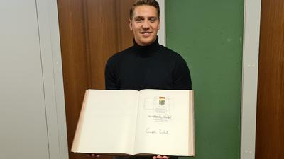 Stolz präsentiert Cem Hancioglu die Unterschrift der ersten Bundeskanzlerin im Goldenen Buch der Stadt.