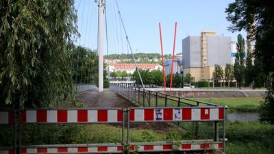 Gesperrter Römersteg im Enzauenpark  mit Blick auf die St. Maur-Halle, den Kohlenbunker (hinten quer), den Wartbergturm und das Heizkraftwerk (rechts).