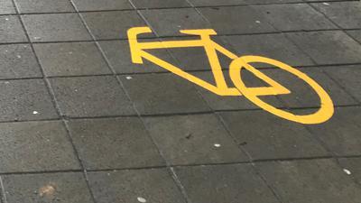 Ein Fahrradsymbol ist auf die Straße geklebt, dabei fehlt das Vorderrad.