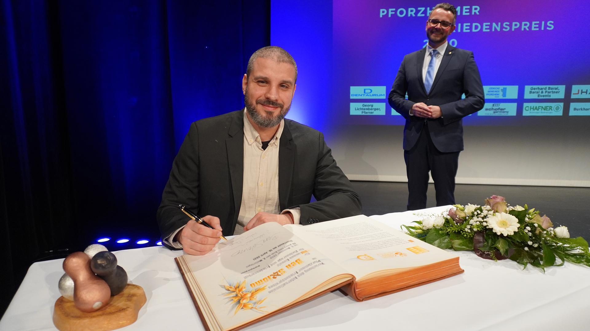 Erster Preisträger: Ben Salomo alias Jonathan Kalmanovich ist als erster Preisträger mit dem Internationalen Pforzheimer Friedenspreis ausgezeichnet worden. Bei der Preisverleihung mit OB Peter Boch (rechts) im Kulturhaus Osterfeld trug er sich ins goldene Buch der Stadt ein.