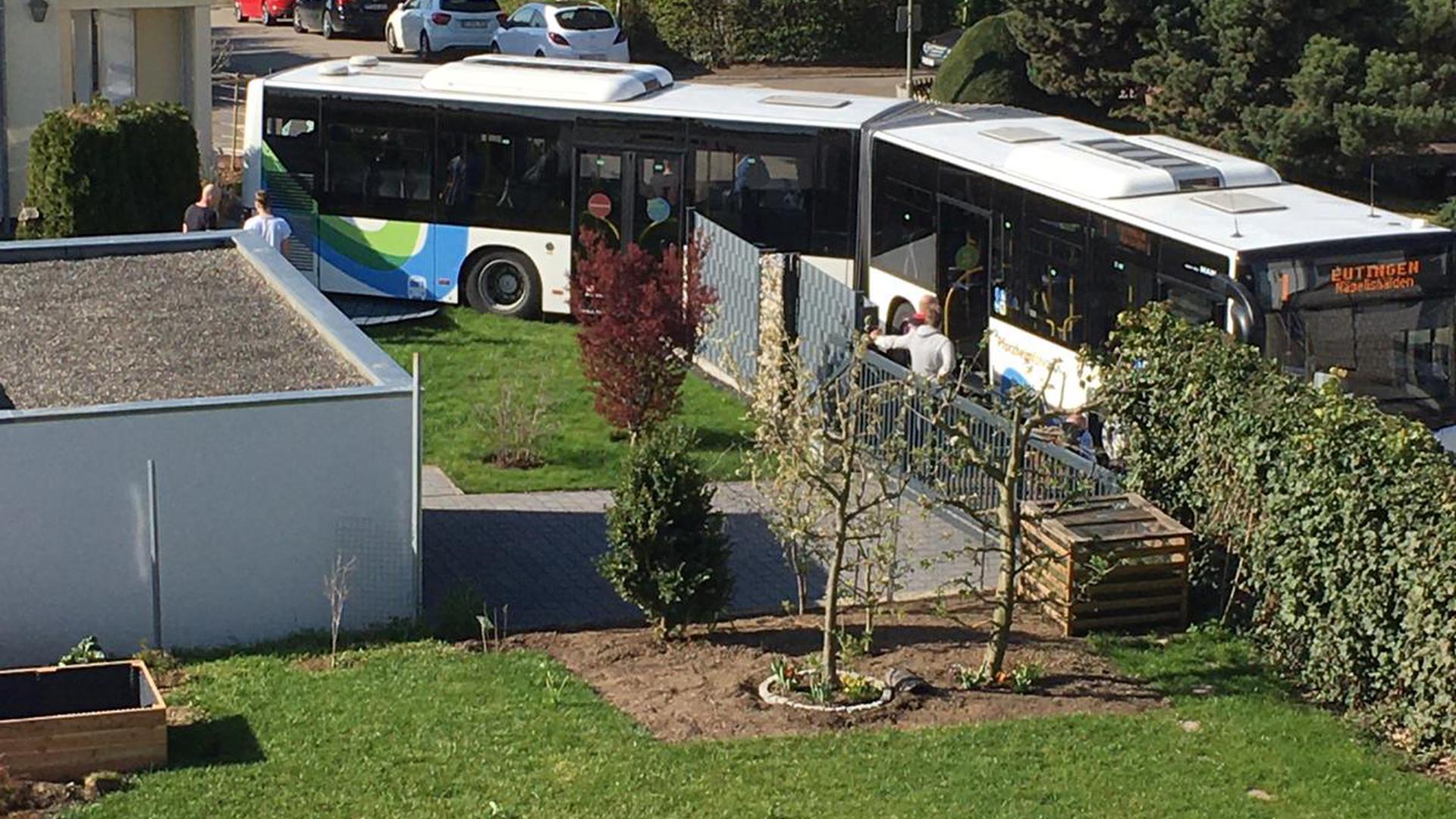 Ein Gelenkbus steht mit dem Heck im Garten vor Reihenhäusern.