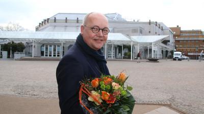 Ein Mann steht vor dem Theater, er hält Blumen in der Hand.