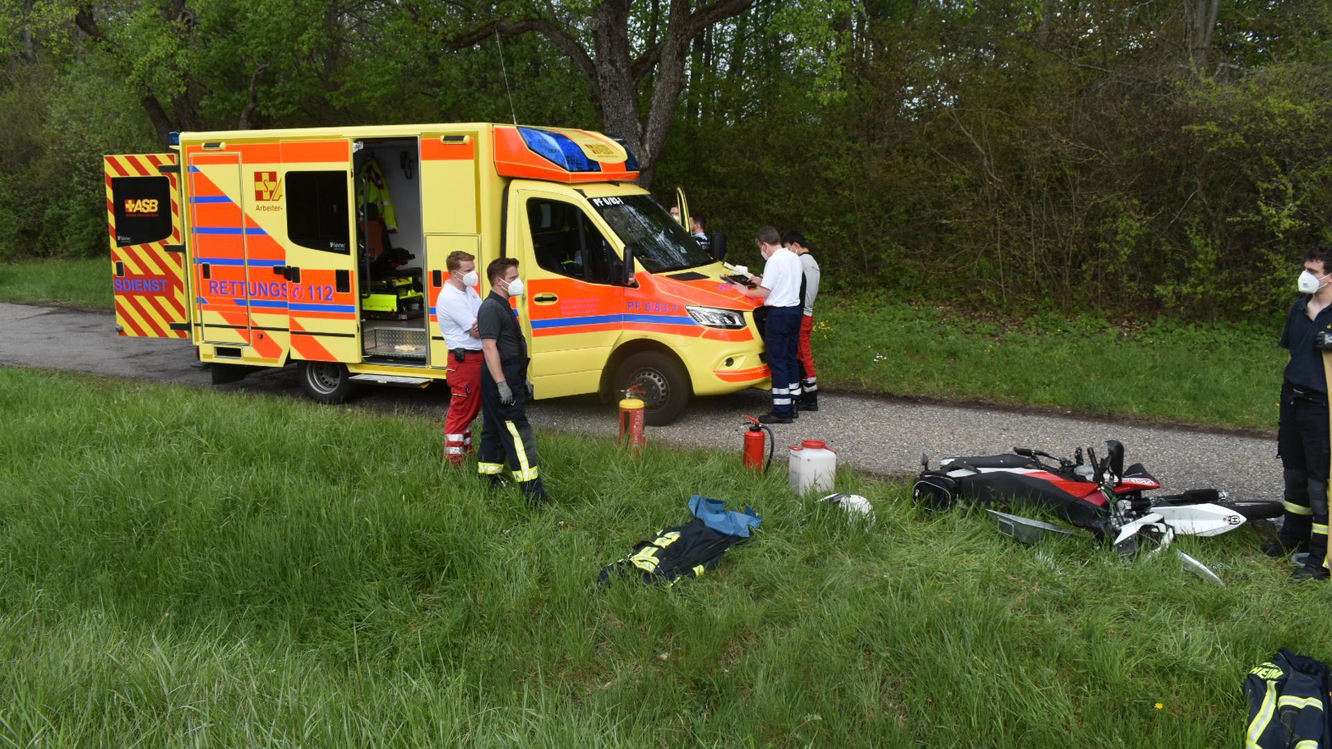 Ein rotes Motorrad liegt auf einer Wiese. Im Hintergrund ein Rettungswagen und mehrere Ersthelfer mit Mundschutz.