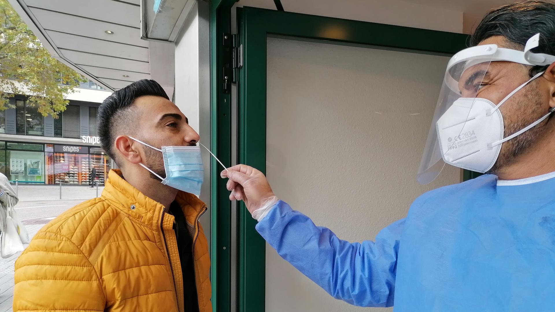 Ein Mann führt per Nasenabstrich einen Corona-Test bei einem anderen Mann durch.