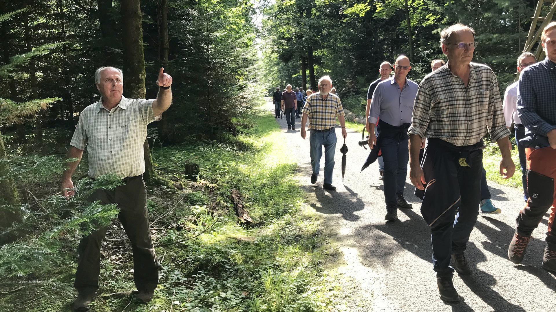 Mehrere Menschen laufen durch einen Wald, ein Mann zeigt mit dem Zeigefinger.