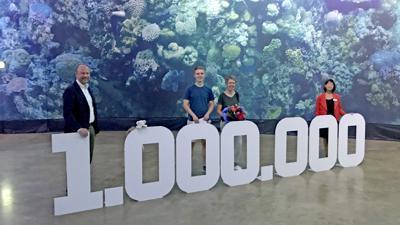 Mehrere Personen stehen hinter einer großen, aufgebauten 1.000.000. Im Hintergrund ist das Panorama mit dem Great Barrier Reef zu sehen.