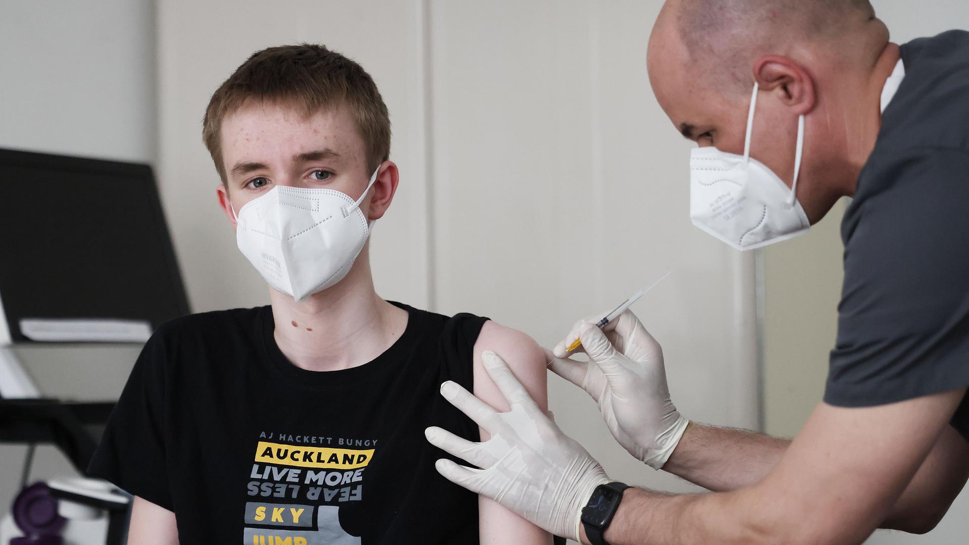 Jan Wolters (15) wird in einer Arztpraxis von dem Hausarzt Tim Koop (r) mit dem Serum von Biontech/Pfizer zu verabreichen. Die Ständige Impfkommission empfiehlt dies aber nur, wenn Vorerkrankungen vorliegen.