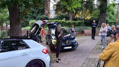 Eine Frau steht vor drei Autos und spricht ins Mikrofon, vor ihr stehen mehrere Menschen.