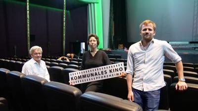 Drei Personen stehen in einem Kinosaal