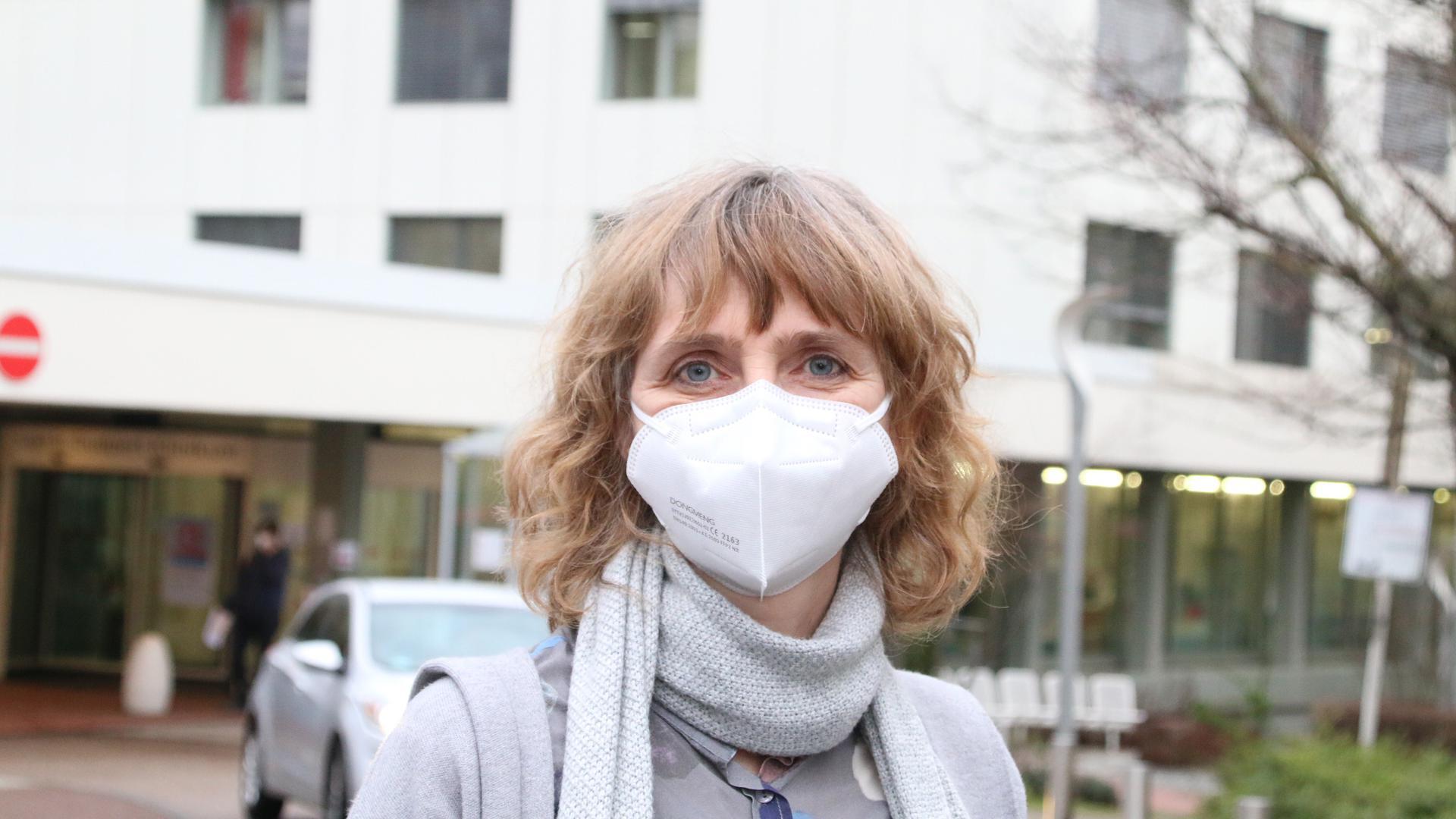 Frau mit Maske vor Klinikum
