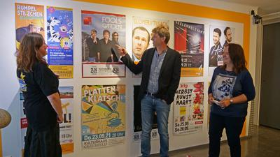 Ein Mann und zwei Frauen vor Plakaten zu Kultur-Veranstaltungen