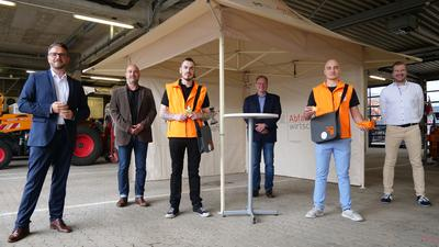 Mehrere Männer stehen vor einem Pavillon.