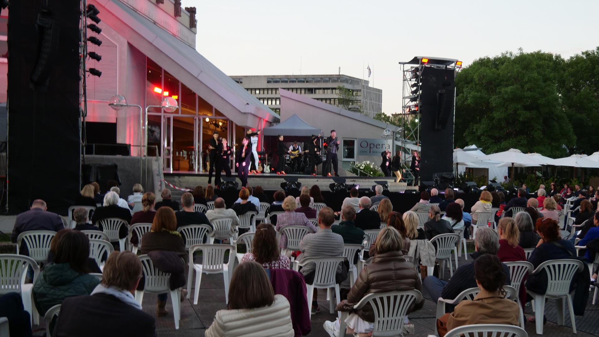 Blick auf eine Bühne, vor der mehrere Menschen auf Plastikstühlen sitzen.