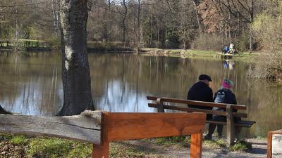 Am Pforzheimer Seehaus sitzen zwei Senioren auf einer Bank.