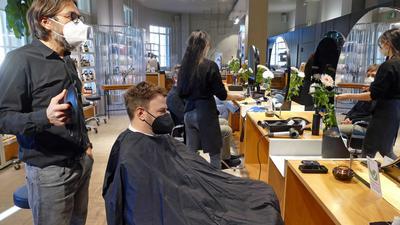Ein Mann sitzt auf einem Frisierstuhl im Salon, hinter ihm steht ein weiterer Mann und hält ihm den Spiegel hin. Im Hintergrund sieht man eine Frau von hinten sowie eine weitere Person in einem Frisierstuhl.