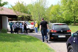 Mehrere Menschen und Autos vor einem Gebäude
