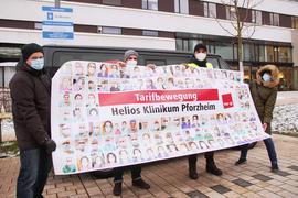 Vier Menschen halten ein Plakat.
