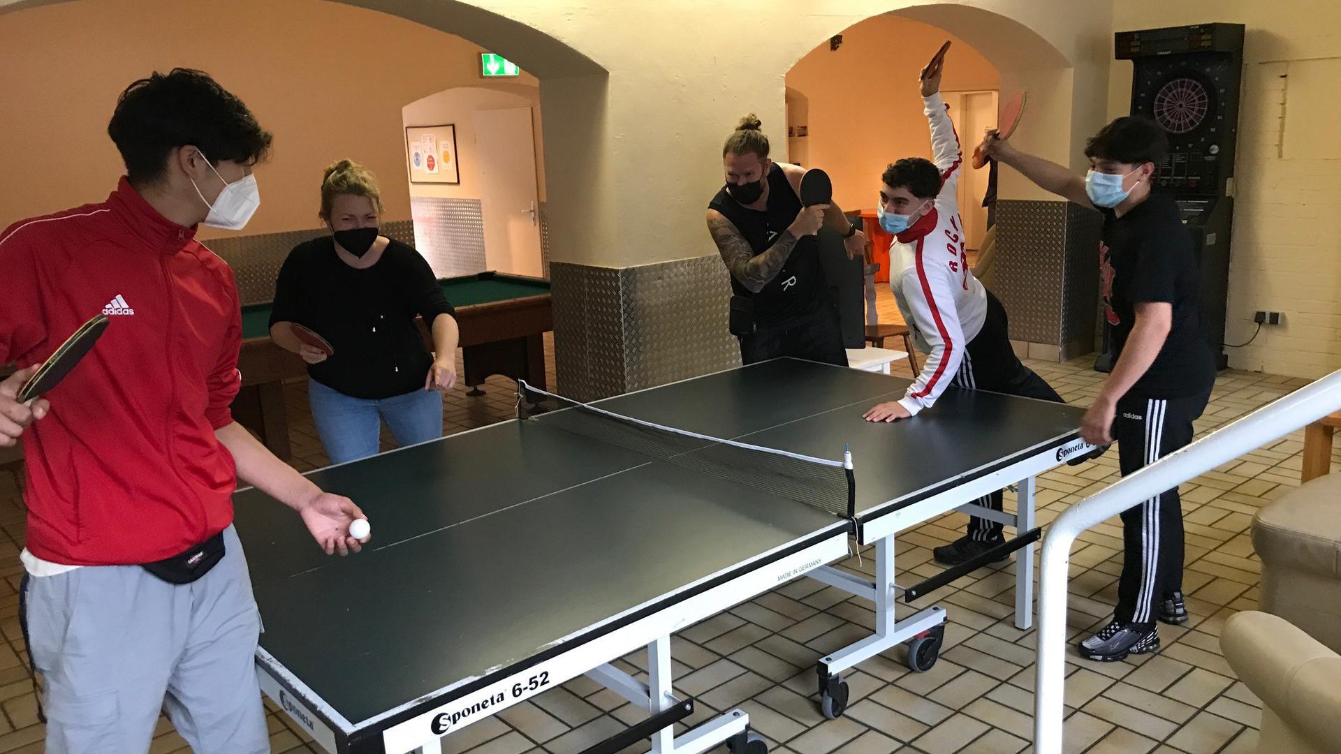 Junge Leute an der Tischtennisplatte